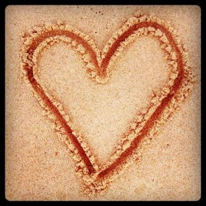 Draw a love heart in the sand