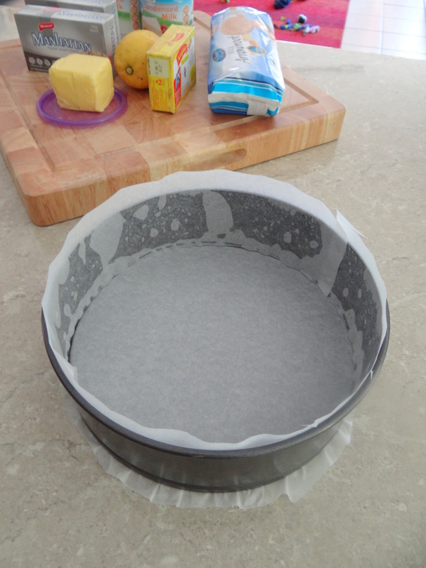 Easy Lemon Cheesecake Recipe -- Spray the inside of a 22cm springform tin with oil.  Line the base & sides with baking paper as shown below.
