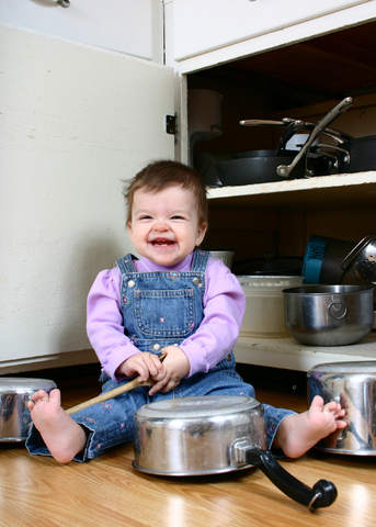 toddler playing with saucepans