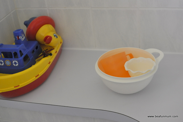 different bath toys -- plastic cups and bowls